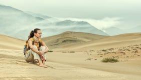 坐和看沙漠谷的少妇 免版税库存图片