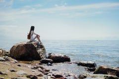 坐和看海的孤独的妇女 免版税库存照片