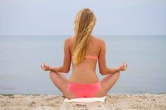 坐和看海的比基尼泳装的美丽的女孩 瑜伽和遇见黎明 库存图片