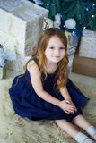 坐和看照相机的一身庄重装束的小女孩 免版税库存图片