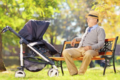 坐和看他的婴儿推车的祖父小侄子 图库摄影