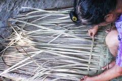 坐和编织一张芦苇席子,手工制造泰国样式的老年人 免版税库存照片