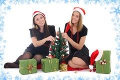坐和装饰结构树的二个女孩 免版税库存图片
