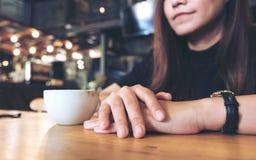 坐和认为在与一杯白色咖啡的咖啡馆的妇女拍手一` s手的特写镜头图象 免版税库存图片