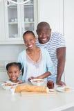 坐和采取早餐的一个愉快的家庭的画象 免版税库存图片