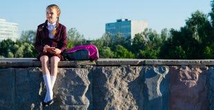 坐和采取笔记的女孩在学校以后,户外 免版税库存照片