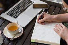 坐和采取笔记的特写镜头商人 免版税图库摄影