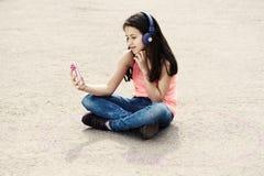 坐圈子个人空间的逗人喜爱的女孩耳机 库存图片