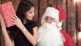 坐圣诞老人`膝部和检查她的礼物的可爱的年轻浅黑肤色的男人 库存照片