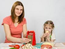 坐在一个五年女儿旁边的厨房用桌t乳酪磨丝器的女孩和吃乳酪 免版税库存图片