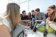 坐在一个创造性的办公室的小组主动的青年人 免版税库存照片