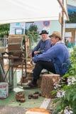 坐在一个古老机器旁边的人打谷五谷 免版税库存照片
