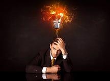 坐在一个吹的想法电灯泡下的商人 免版税库存图片