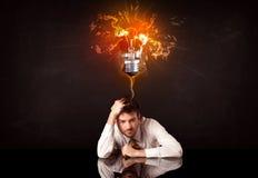 坐在一个吹的想法电灯泡下的商人 免版税库存照片