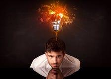 坐在一个吹的想法电灯泡下的商人 免版税图库摄影