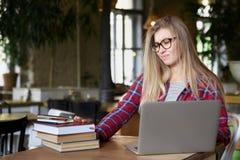 坐在一个咖啡馆的一张桌上的年轻学生女孩与课本和膝上型计算机 她对学习是疲乏 免版税图库摄影