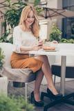 坐在一个咖啡馆的年轻可爱的妇女早晨在h前 免版税图库摄影