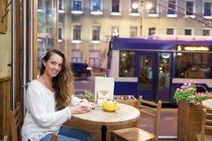 坐在一个咖啡馆的晚上的年轻可爱的女孩与一杯茶对通过汽车和城市生活背景  她看 免版税图库摄影