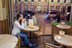 坐在一个咖啡馆的晚上的年轻可爱的女孩与一杯茶对通过汽车和城市生活背景  她看 免版税库存照片