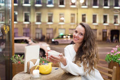 坐在一个咖啡馆的晚上的年轻可爱的女孩与一杯茶对通过汽车和城市生活背景  她看 图库摄影