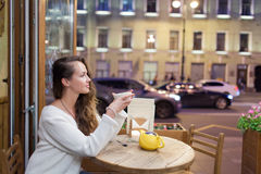 坐在一个咖啡馆的晚上的年轻可爱的女孩与一杯茶对通过汽车和城市生活背景  库存照片
