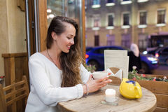 坐在一个咖啡馆的晚上的年轻可爱的女孩与一杯茶对通过汽车和城市生活背景  免版税图库摄影