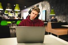 坐在一个咖啡馆的耳机和便服的英俊的年轻人与膝上型计算机和集中于屏幕 免版税图库摄影