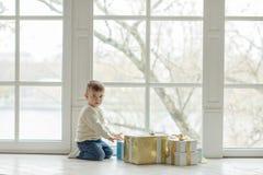 坐在一个大窗口附近的迷人的小男孩小孩近 库存照片