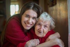 坐在一个成人孙女的拥抱的一名年长妇女 爱 库存照片