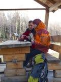 坐在一个木眺望台在桌上和饮料的游人从 图库摄影
