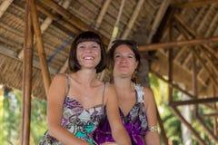坐在一个木眺望台的两个美丽的愉快的女孩晴天 并且有乐趣,微笑和笑 热带 免版税图库摄影