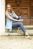坐在一个木门前面的妇女画象 免版税图库摄影