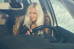 坐在汽车的轮子的之后性感的女孩 库存照片