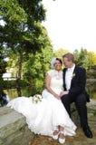 坐在一个湖的新娘和新郎在秋天 免版税图库摄影