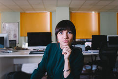 坐在一个现代办公室和看照相机的工作者年轻美丽的妇女 3d背景镜象人寿保险业白色 库存照片