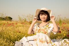 坐在一个用花装饰的草甸的愉快的女孩夏令时 免版税库存照片