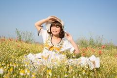 坐在一个用花装饰的草甸的愉快的女孩夏令时 免版税库存图片