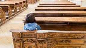 坐在一个空的教会里的年轻女人 免版税库存图片