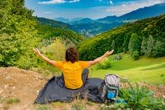 坐在一个美好的山风景的一条防水尼龙毯子和享受看法,与胳膊的年轻山徒步旅行者 免版税库存照片