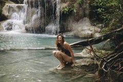 坐在一个自然池塘的妇女 免版税库存图片
