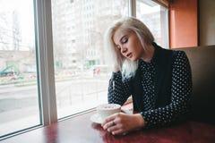 坐在一个舒适咖啡馆的一名年轻美丽的白肤金发的妇女的画象在与一杯咖啡的窗口附近 背景中断咖啡新月形面包杯子甜点 库存照片