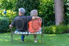 坐在一个豪华的绿色庭院里的年长夫妇 库存图片