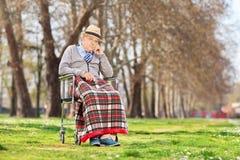 坐在一个轮椅的脾气坏的老人在公园 免版税库存图片