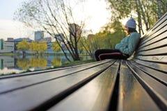 坐在一个长木凳边缘的女孩在城市公园 库存照片