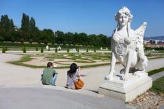 坐在一个雕塑下的年轻夫妇在Schonbrunn宫殿从事园艺 库存照片