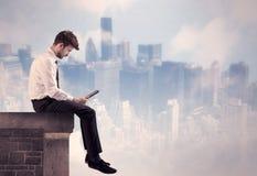 坐在一个高楼顶部的销售人 库存照片