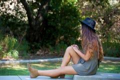 坐在一个围场的女孩 库存图片