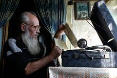 坐在一台古色古香的留声机附近的玻璃的胡须半白的老人老人 免版税库存图片