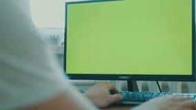 坐在一台大屏幕显示器前面的一个中年人的背面图 绿色屏幕 键盘 影视素材