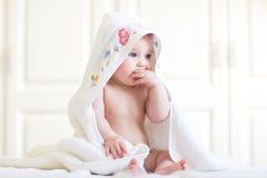坐在一块戴头巾毛巾下的可爱的女婴在浴以后 图库摄影